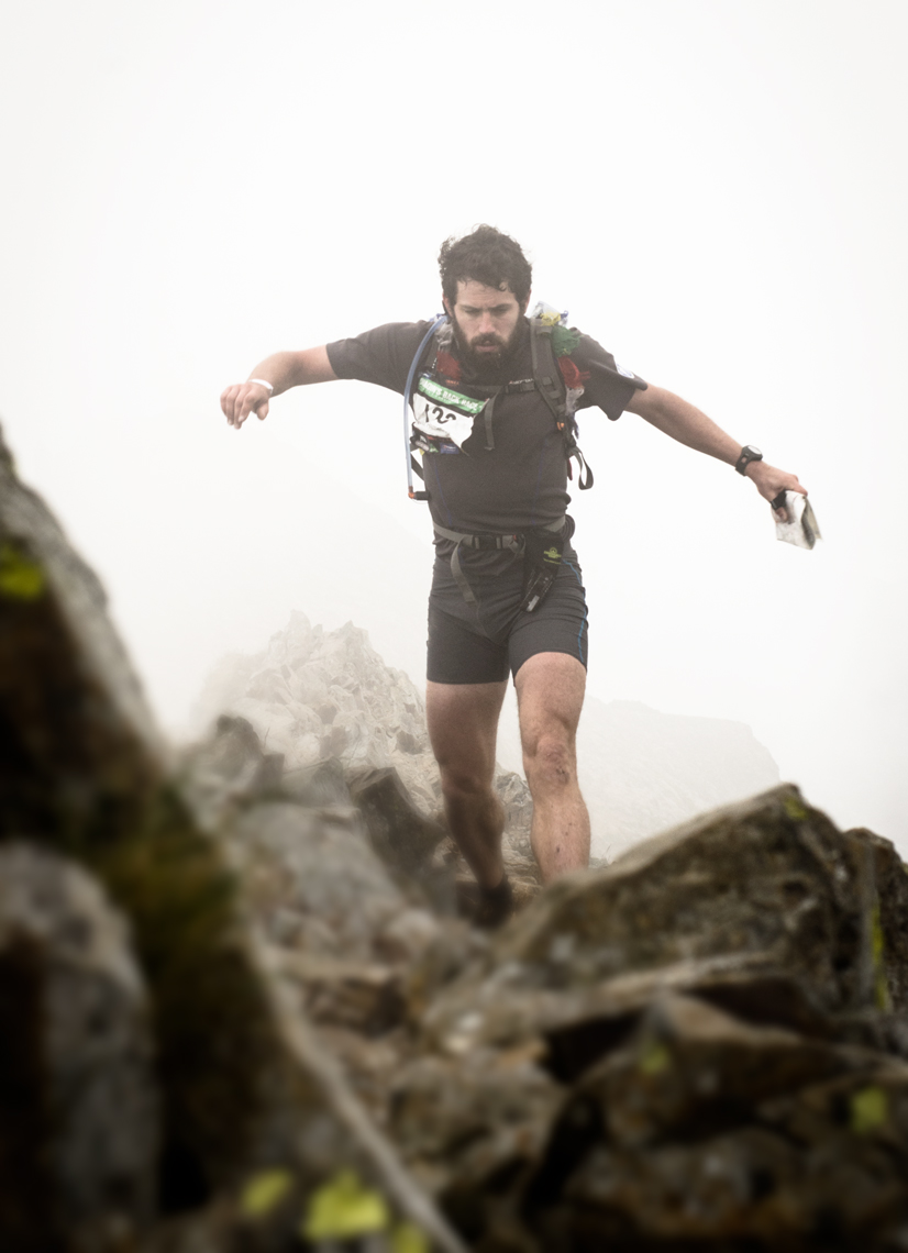 Runners emerge from the mist high on Snowdonia